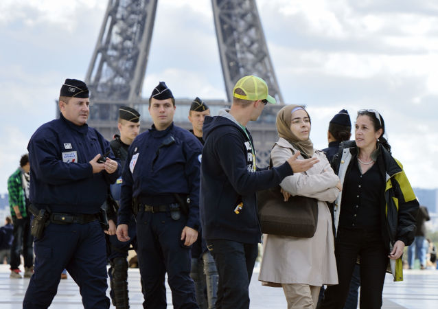 French mobile policemen talk with a Muslim woman control on the Trocadero square in Paris, on September 22, 2012