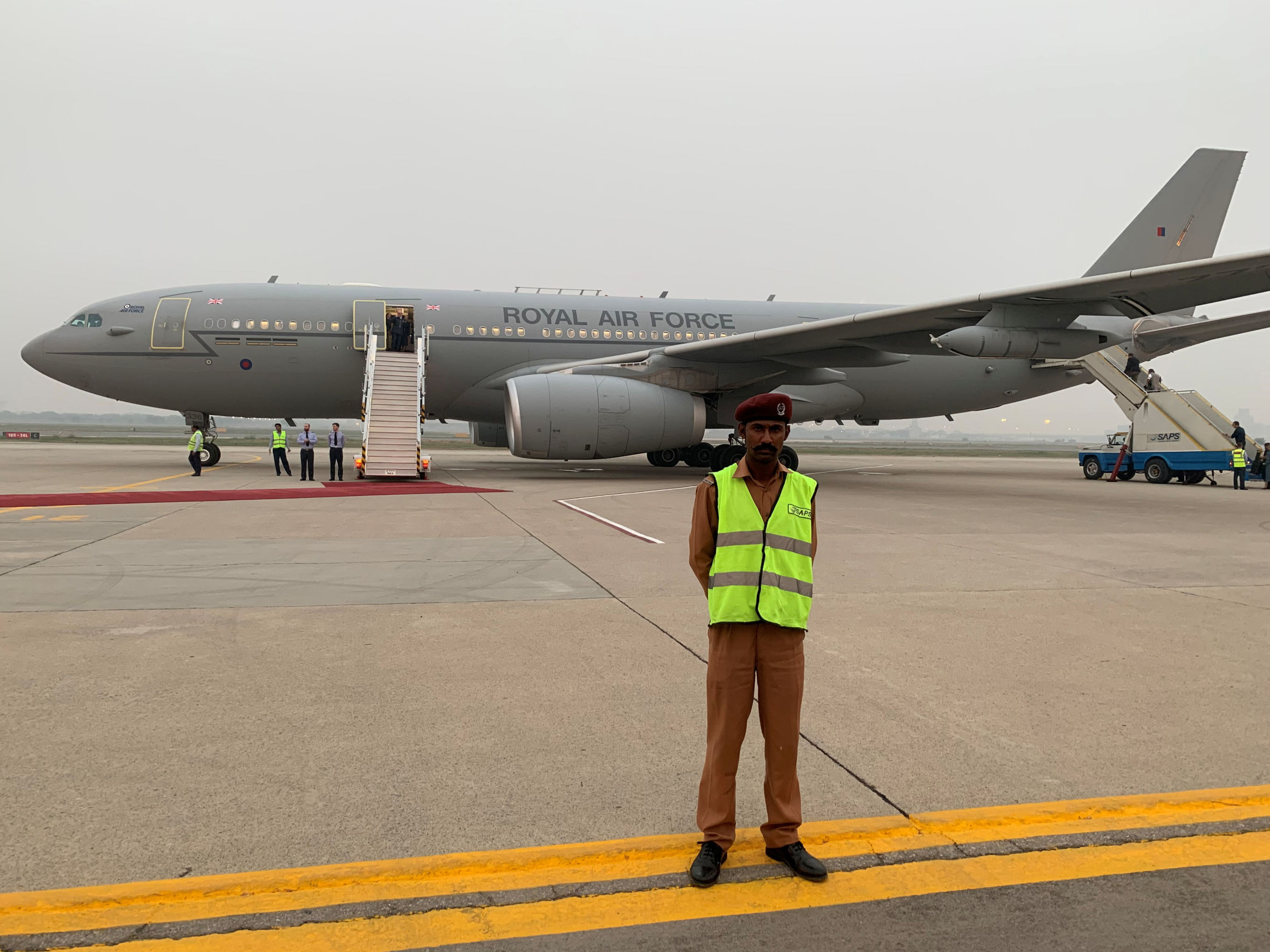 Pakistani security is seen on the tarmac in front of the Royal Air Force plane in Lahore, Pakistan, October 17, 2019. The Royal Air Force plane carrying the royal couple was forced to abort a landing in Islamabad twice on Thursday and return to Lahore after being caught in a severe thunderstorm.