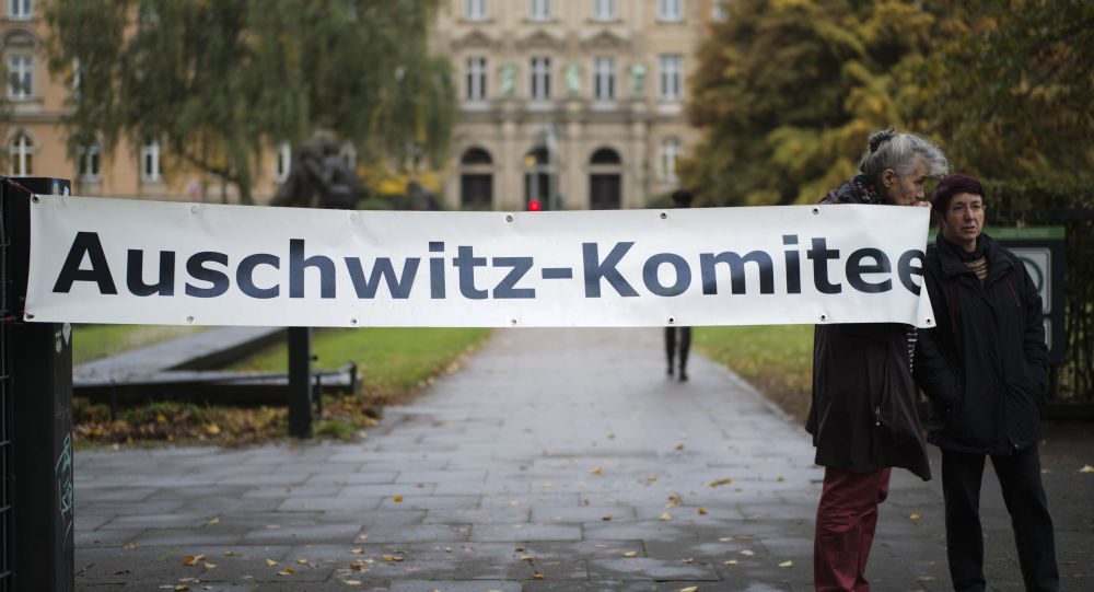 Two women of the Auschwitz Committee show a poster near the criminal court in Hamburg, Thursday, Oct. 17, 2019. 93-year-old former SS private Bruno Dey is going on trial at the court on 5,230 counts of being an accessory to murder, accused of helping the Nazis' Stutthof concentration camp function. (AP Photo/Markus Schreiber)