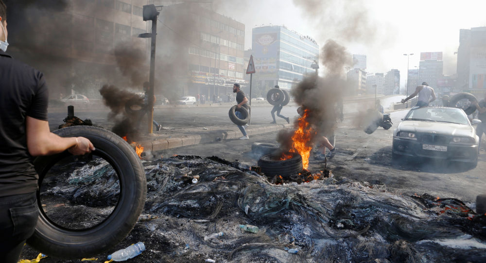 Demonstrators run as they hold tires during a protest over deteriorating economic situation, in Dora, Lebanon October 18, 2019