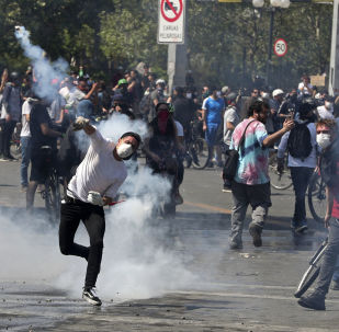 A protester returns a tear gas canister to police during clashes in Santiago, Chile, Sunday, Oct. 20, 2019. Protests in the country have spilled over into a new day, even after President Sebastian Pinera cancelled the subway fare hike that prompted massive and violent demonstrations. (AP Photo/Esteban Felix)