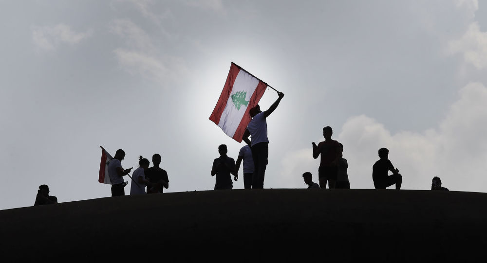 Anti-government protesters wave a Lebanese flag, as they stand on the Dome City Center known as The Egg, an unfinished cinema leftover from the civil war, as they watch other protesters, in downtown Beirut, Lebanon, Sunday, Oct. 20, 2019. Tens of thousands of Lebanese protesters of all ages gathered Sunday in major cities and towns nationwide, with each hour bringing hundreds more people to the streets for the largest anti-government protests yet in four days of demonstrations. (AP Photo/Hussein Malla)