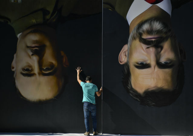 A man sets up upside down giant paintings of late Spanish dictator Francisco Franco, left, and Spanish King Felipe VI ahead of a protest by Basque pro-independence activists in support of Catalonia's independence movement following Spain's conviction of Catalan separatist leaders, in Bilbao, northern Spain, Tuesday, Oct. 15, 2019