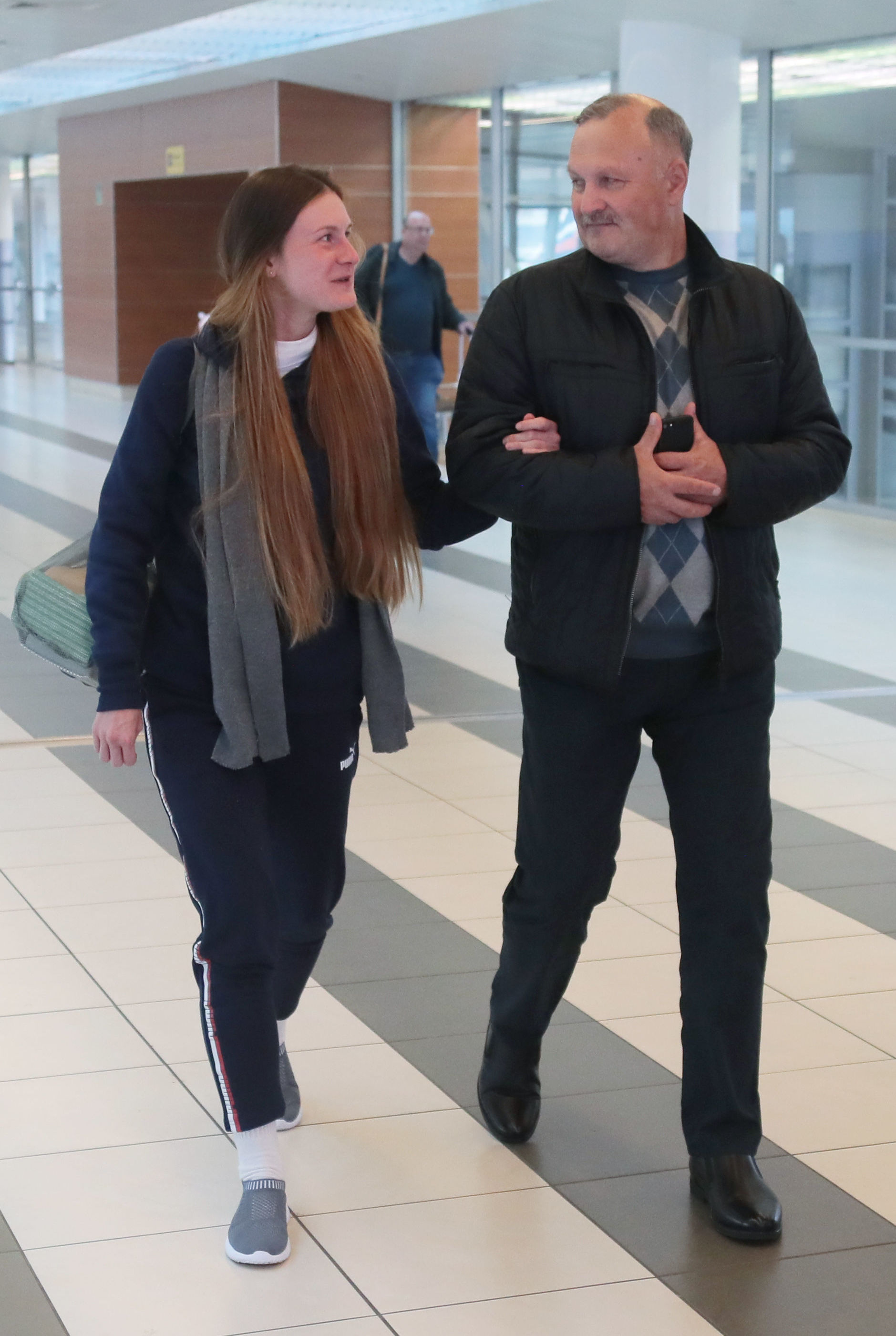 Convicted Russian agent Maria Butina, who was released from a Florida prison and then deported by U.S. immigration officials, walks with her father Valery Butin upon her arrival at Sheremetyevo International Airport outside Moscow