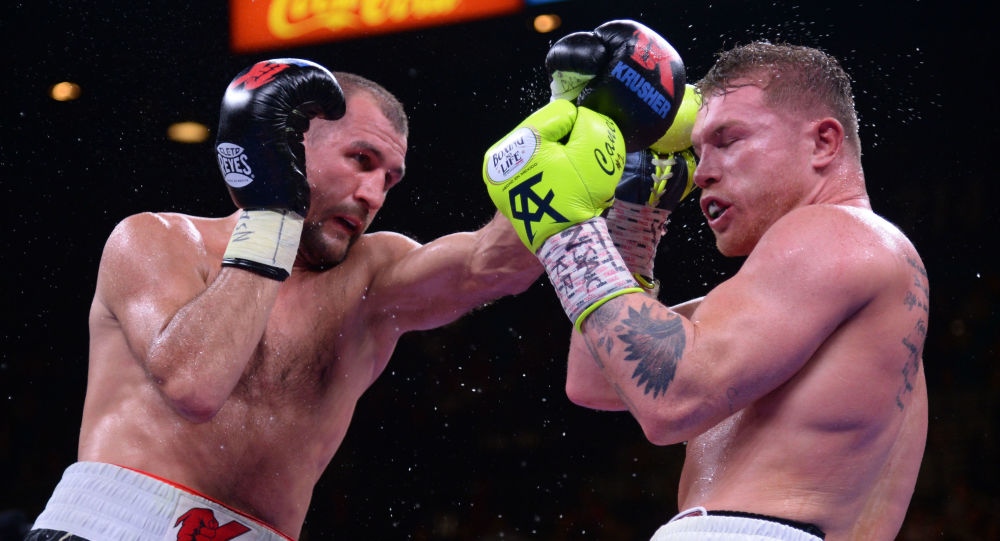 Canelo Alvarez (blue/green trunks) and Sergey Kovalev (black/white/red trunks) box during their WBO light heavyweight title bout at MGM Grand Garden Arena in Las Vegas, Nevada, 2 November 2019