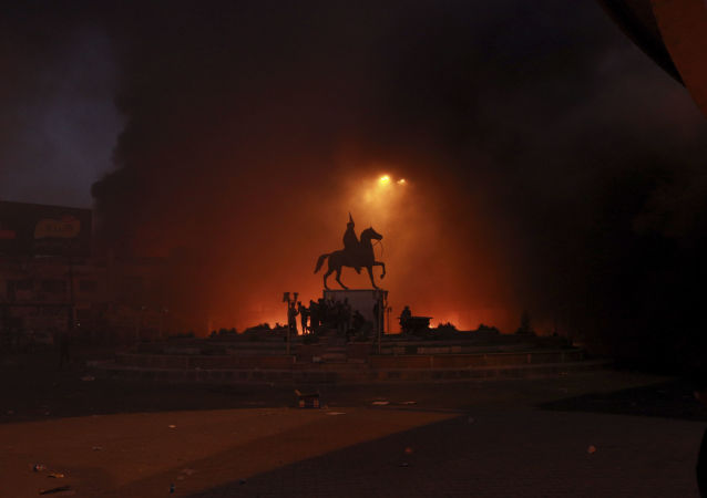 Anti-government protests set fire while security forces fired live ammunition and tear gas near the state-run TV in Baghdad