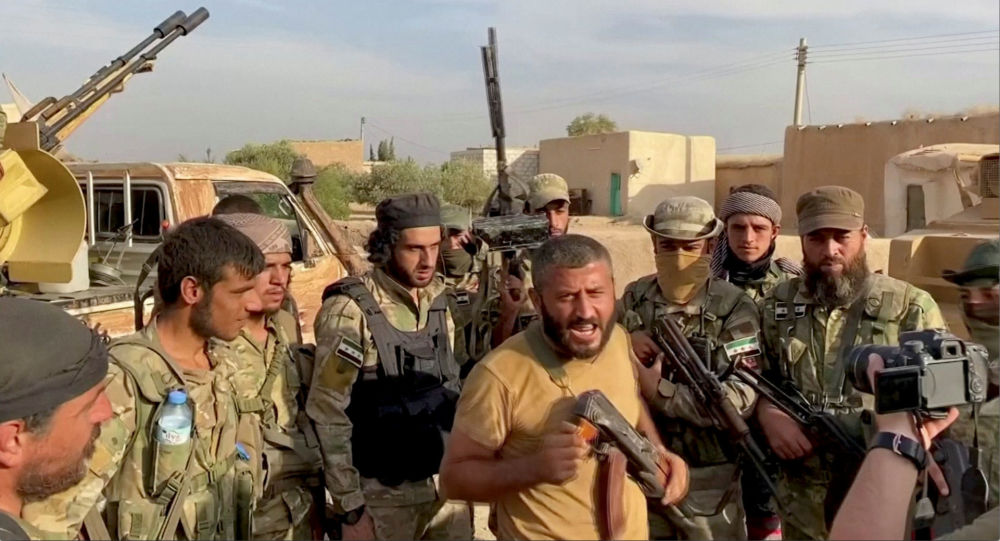 A Syrian rebel fighter declares the liberation of Mehrabli village from the Syrian Democratic Forces (SDF) near Tal Abyad, Syria, October 11, 2019, in this still image obtained from video