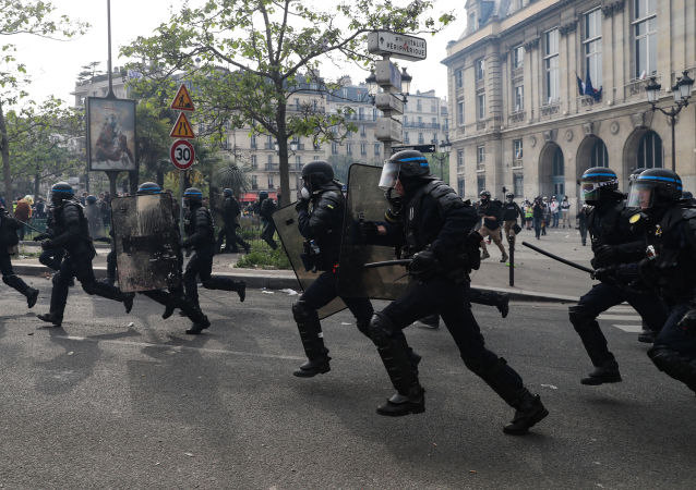 French anti-riot policemen run during clashes with protesters on the sidelines of the annual May Day rally in Paris on May 1, 2019