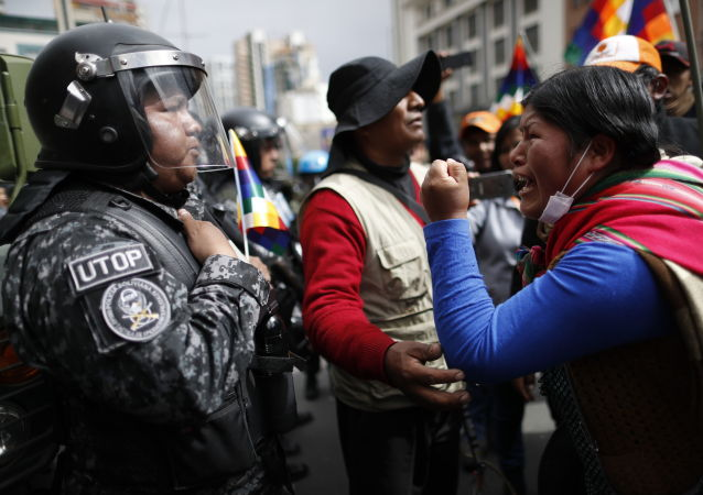 A supporter of Bolivia's former President Evo Morales yells at a police officer, telling him to respect the nation's indigenous people in La Paz, Bolivia, Tuesday, Nov. 12, 2019. Former President Evo Morales, who transformed Bolivia as its first indigenous president, flew to exile in Mexico on Tuesday after weeks of violent protests, leaving behind a confused power vacuum in the Andean nation. (AP Photo/Natacha Pisarenko)