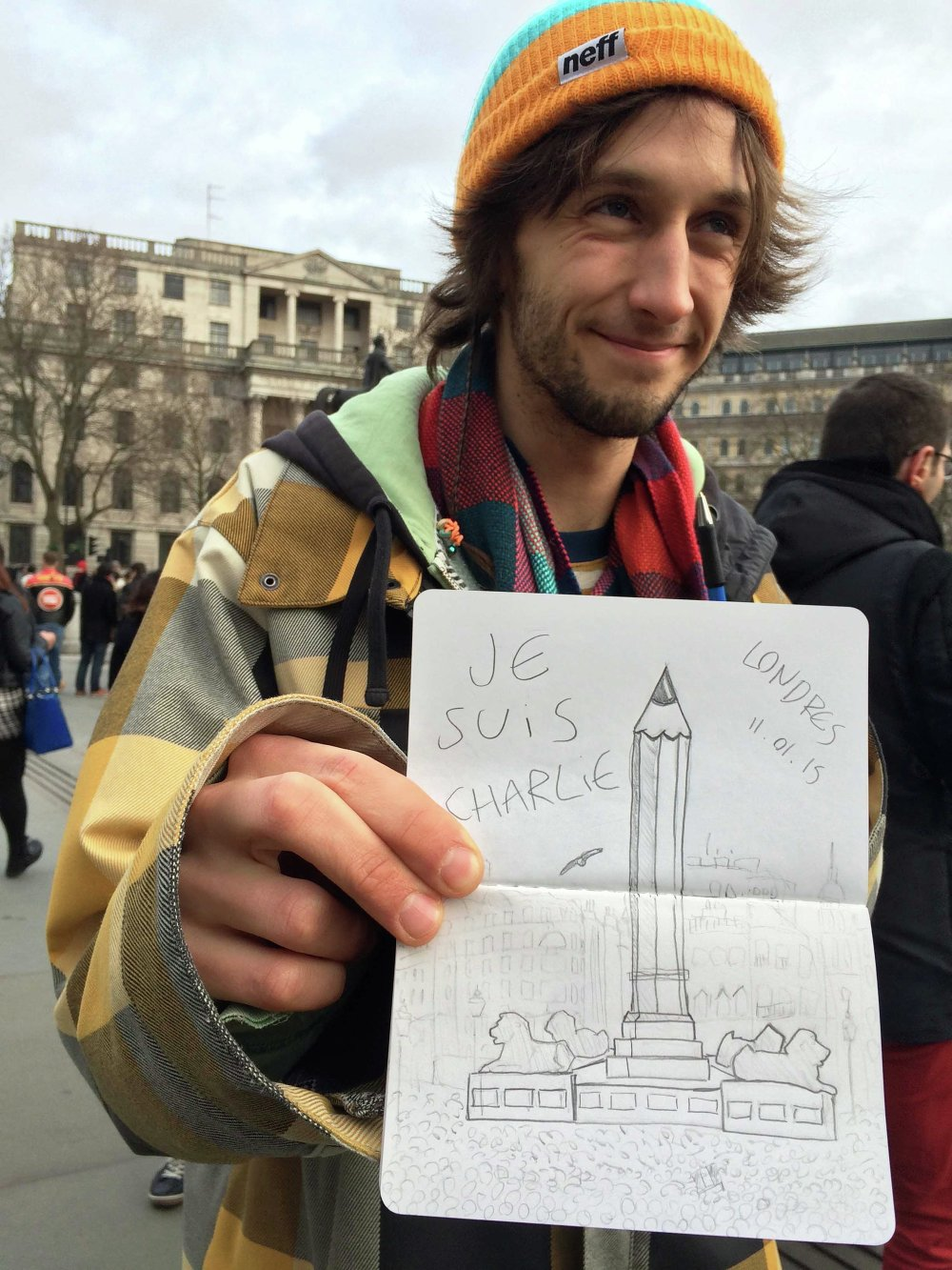 A man holds a sketch of Trafalgar Square and the words 'Je Suis Charlie'.