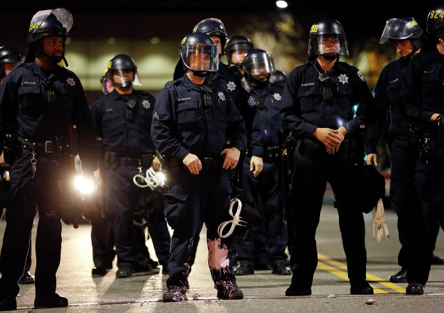 A police officer looks into the crowd, after he was hit on the leg with paint thrown by protesters during an evening demonstration against police violence, in Oakland, California December 13, 2014
