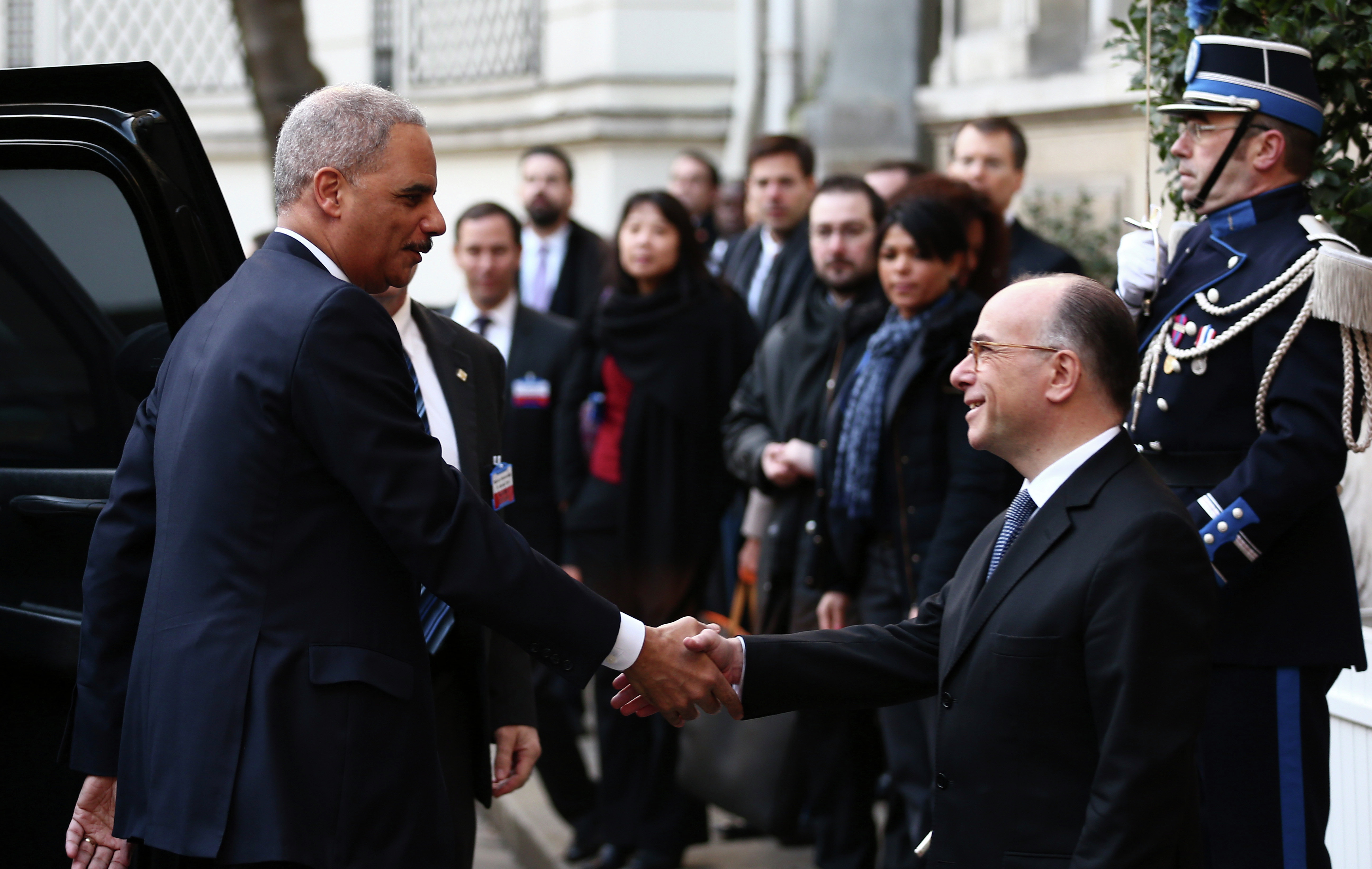 U.S Attorney General Eric Holder, left, is welcomed by French Interior Minister Bernard Cazeneuve before the start of an international meeting aimed at fighting terrorism, in Paris, France, Sunday, Jan. 11, 2015. A rally of defiance and sorrow, protected by an unparalleled level of security, on Sunday will honor the 17 victims of three days of bloodshed in Paris that left France on alert for more violence.