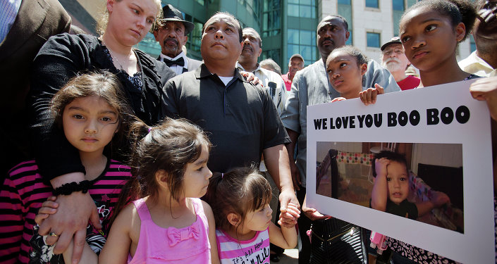 Alecia and Boun Khan Phonesavanh, from rear left, the parents of 19-month-old Bounkham Phonesavanh who was severely burned by a flash grenade during a SWAT drug raid, attend a vigil with their daughters outside Grady Memorial Hospital where he is undergoing treatment, Monday, June 2, 2014, in Atlanta.