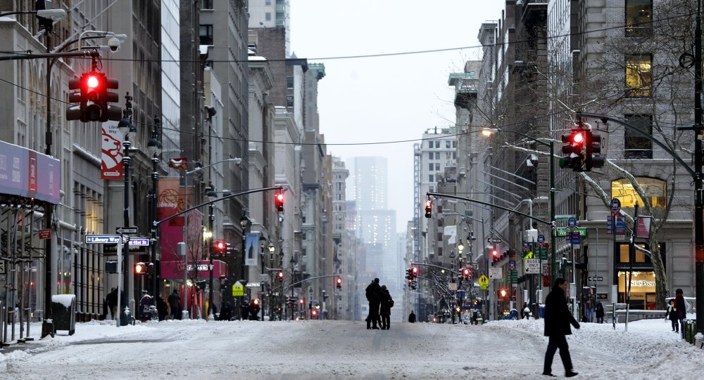 People walk in the middle of a car-free Fifth Avenue in New York, Tuesday, Jan. 27, 2015. A storm packing blizzard conditions spun up the East Coast early Tuesday, pounding parts of coastal New Jersey northward through Maine with high winds and heavy snow.