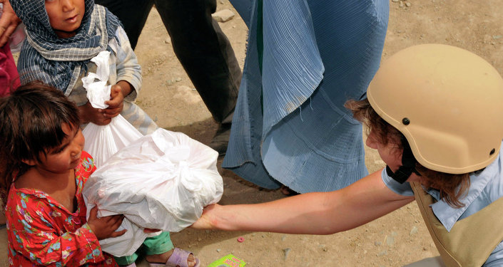 An Afghan girl accepts a bag of supplies from a volunteer duirng a humanitarian mission at an Afghan refugee camp