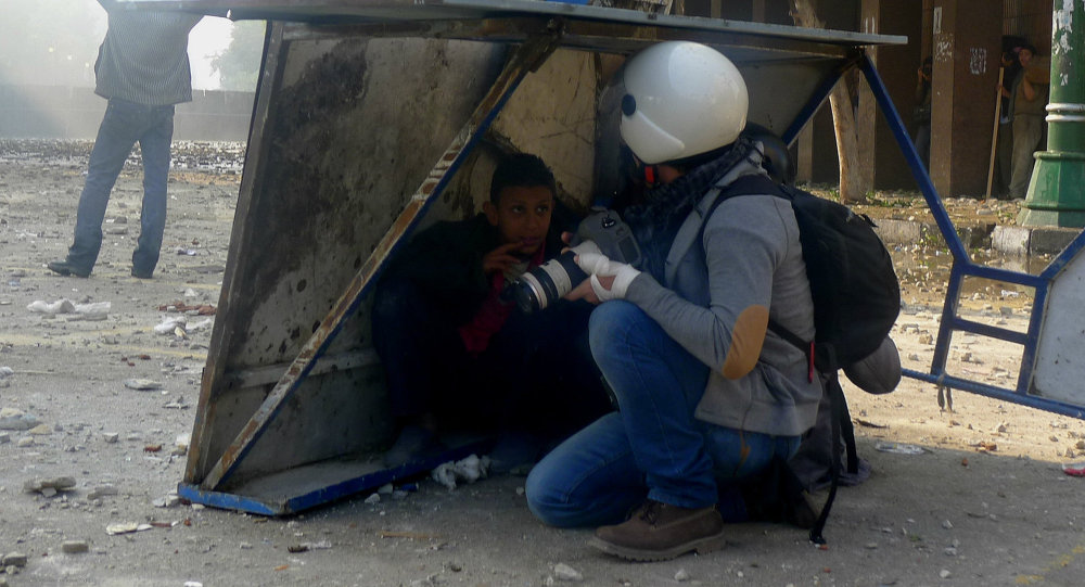 Journalist and boy take cover from stones thrown by rooftop militia