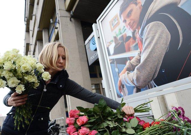 Коллега возлагает цветы в память о погибшем на Украине фотокорреспонденте Андрее Стенине у здания МИА Россия сегодня
