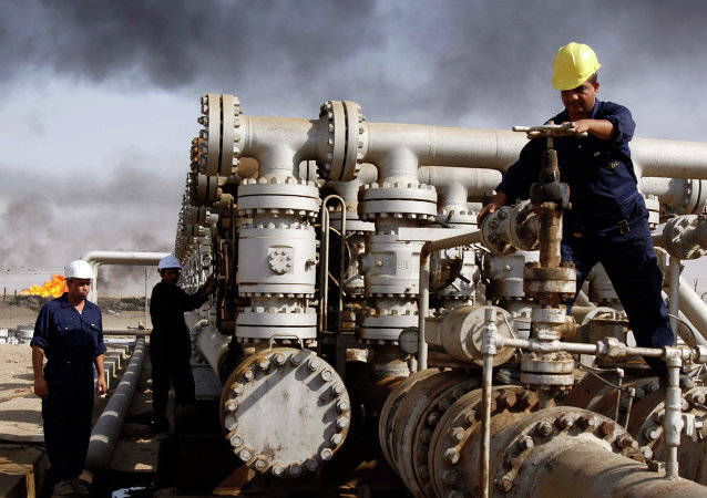 Iraqi laborers work at the Rumaila oil refinery, near the city of Basra