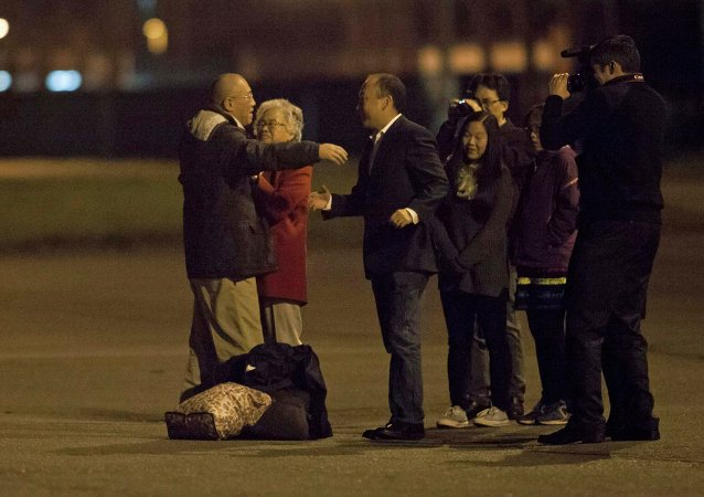 Kenneth Bae (L) reunites with his family at U.S. Air Force Joint Base Lewis-McChord in Fort Lewis, Washington