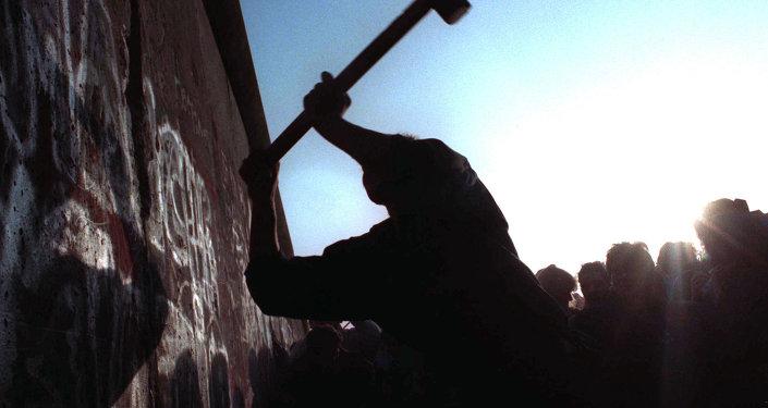 Человек бьет молотом по Берлинской стене
