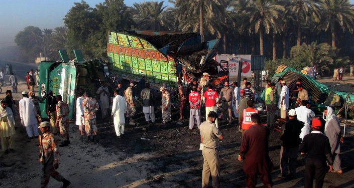 Pakistan paramilitary soldiers and rescue workers gether at the site of bus and truck collision in Khairpur district, Pakistan, Tuesday, Nov. 11, 2014