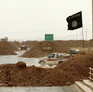 Islamic State militants passing a checkpoint bearing the group's trademark black flag in the village of Maryam Begg in Kirkuk, 290 kilometers (180 miles) north of Baghdad, Iraq