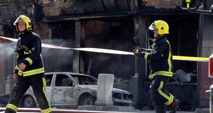 Firefighters prepare the area in front of a burnt builting