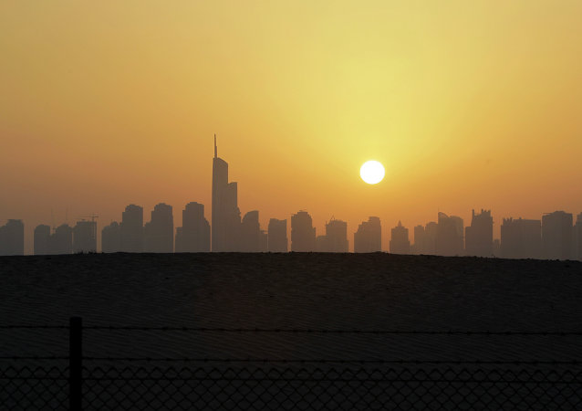 The sun sets behind the city skyline at the Marina district as the Almas tower is seen in Dubai, United Arab Emirates