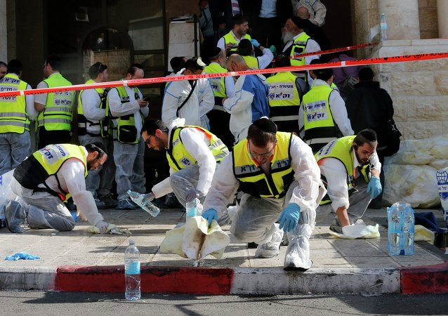 Members of the Israeli Zaka emergency response team clean blood from the scene of an attack at a Jerusalem synagogue