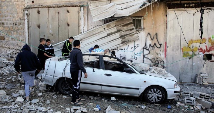 Palestinians stand next to a car damaged during the demolition of Abdel-Rahman Shaloudi's home in the East Jerusalem neighbourhood of Silwan November 19, 2014