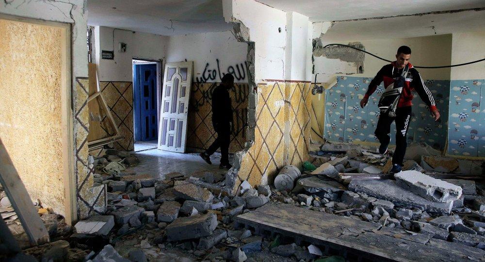 Relatives of Abdel-Rahman Shaloudi walk on rubble in his destroyed home in the East Jerusalem neighbourhood of Silwan November 19, 2014