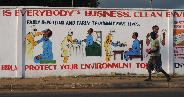 A man walks by a mural with health instructions on treating the Ebola virus, in Monrovia, November 18, 2014