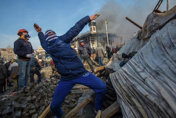 A protester throws stone on Maidan square in Kiev, Ukraine, Feb 19, 2014