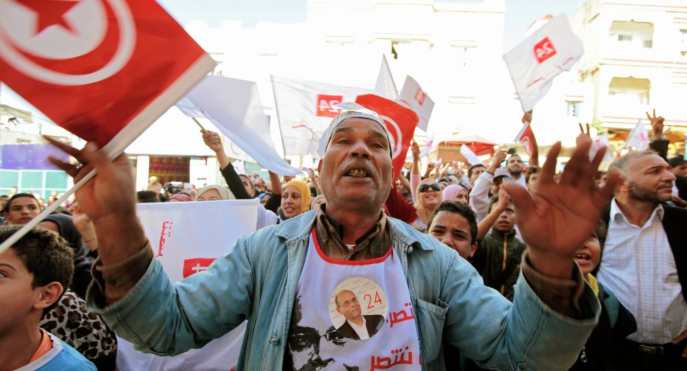 Supporters of Tunisia's President Moncef Marzouki, who is seeking re-election, react during his campaign rally at Hai al Tadamon in Tunis