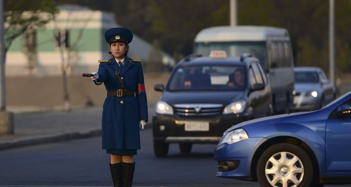 Pyongyang, North Korea: A traffic policewoman directs cars.