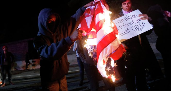 A protester burns an American flag on Highway 580 during a demonstration following the grand jury decision in the Ferguson, Missouri shooting of Michael Brown, in Oakland, California
