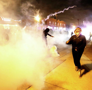 Protesters run from a cloud of tear gas after a grand jury returned no indictment in the shooting of Michael Brown in Ferguson, Missouri,