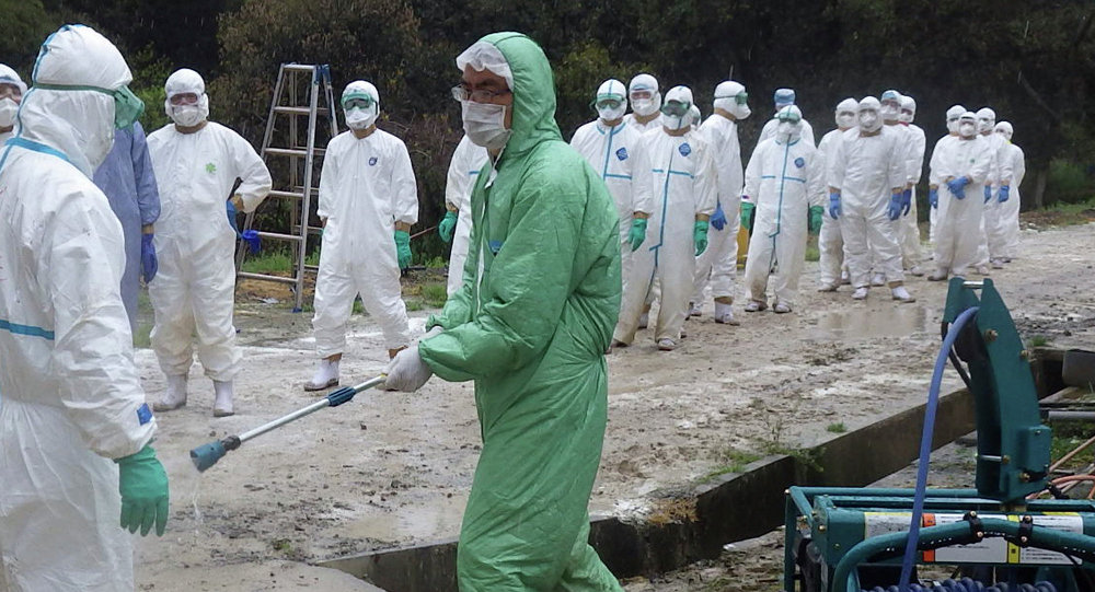 Kumamoto Prefecture, local government workers in white protective overalls line up to be sprayed disinfectant in Taragicho