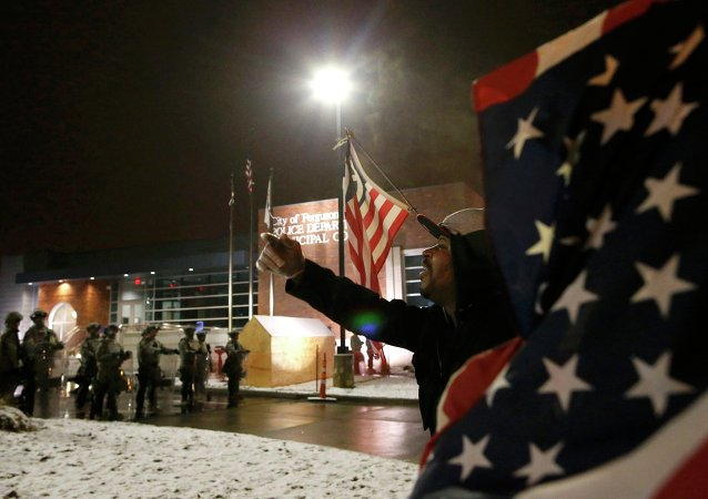 A protester shouts at the National Guard standing on duty outside the Ferguson Police Department after the grand jury verdict in the Michael Brown shooting in Ferguson, Missouri, November 26, 2014