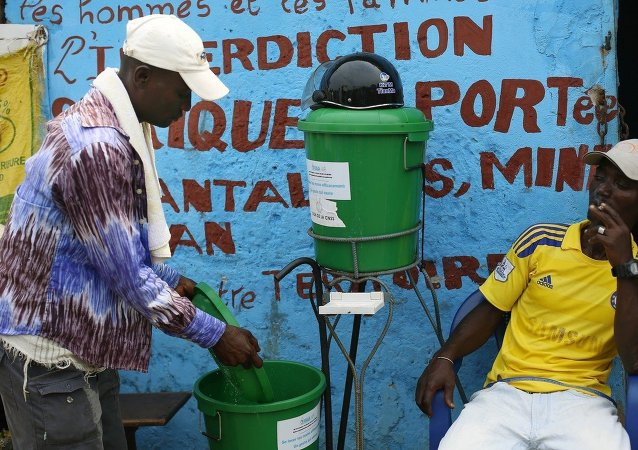Residents wash their hands with chlorinated water at the fishing port of Conakry, Guinea, Tuesday Nov. 25, 2014