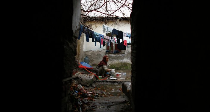 Syrian refugee woman washes the dishes in front of her house in Ankara