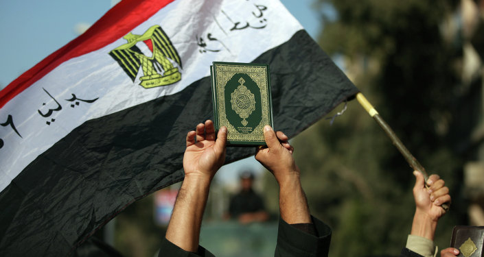 An Egyptian man holds up the a copy of Quran