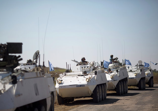 Armored vehicles from the UN peacekeepers of the United Nations Disengagement Observer Force, also known as UNDOF wait to cross from the Israeli controlled Golan Heights to Syria