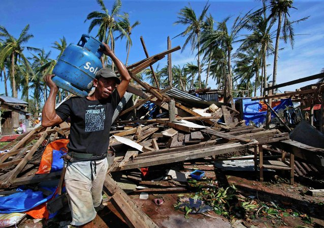 A typhoon victim carries a gas tank for cooking past a house destroyed by Typhoon Hagupit in Borongan city, Samar, in central Philippines December 8, 2014