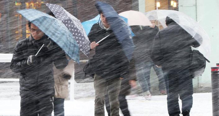 People walk against blowing snow in Tokyo