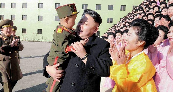 Le dirigeant nord-coréen Kim Jong Un tient un garçon après une séance de photos avec des participants à la deuxième réunion des familles des militaires exemplaires de l'APC dans cette photo non datée publiée par l'Agence de presse coréenne du nord (KCNA) à Pyongyang