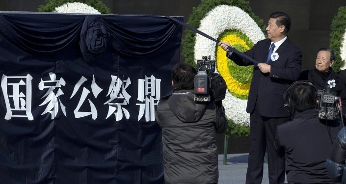 Chinese President Xi Jinping unveils a sculpture of a ceremonial utensil to mark China's first National Memorial Day at the Nanjing Massacre Memorial Hall in Nanjing in eastern China's Jiangsu province Saturday, Dec. 13, 2014