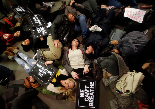 Protesters rallying against a grand jury's decision not to indict the police officer involved in the death of Eric Garner stage a die-in at the Apple Store on Fifth Avenue