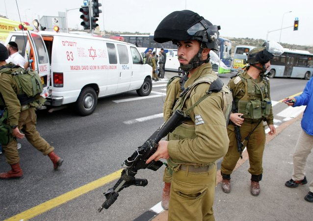 Israeli soldier stand at the scene where a Palestinian attacked civilians with a chemical substance
