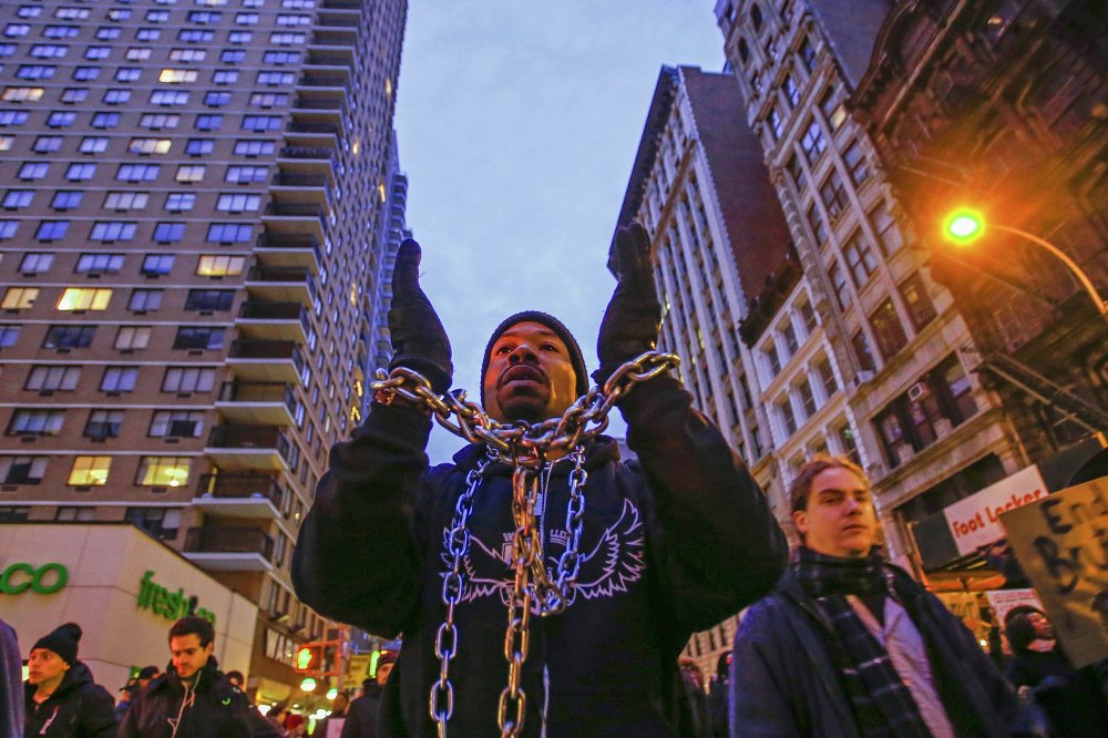 A man with chains around his wrists and neck takes part in a march against police violence, in New York December 13, 2014